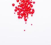 Perles rouges sur l'espace libre blanc de fond Image libre de droits