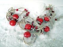 Perles rouges sur une neige images stock