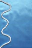Perles sur la soie bleue élégante comme fond Image stock
