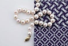 Perlez le collier sur le fond blanc et les clo bleus et blancs d'indigo Photos libres de droits