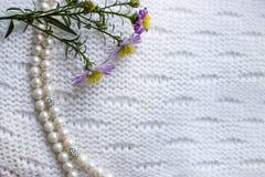 Perlez les perles et une branche des fleurs pourpres d'automne sur un fond blanc tricoté par textile Automne - l'hiver vêtx le co Photo stock
