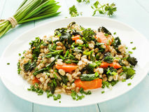 Perlotto. Boiled pearl barley with nettle, carrot and leek. Shallow dof Stock Image