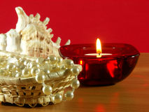 Perls. The candle and pearls on the table. Red background Royalty Free Stock Photo