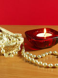 Perls and candle. The candle and pearls on the table. Red background Stock Image