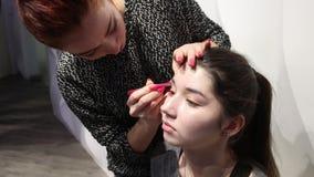 PERM, ΡΩΣΊΑ - 12 ΦΕΒΡΟΥΑΡΊΟΥ 2017: Ο καλλιτέχνης Makeup με την πρότυπη απελευθέρωση μαδά τα φρύδια για το πρότυπο στο γάμο δίκαιο φιλμ μικρού μήκους