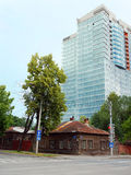 Perm, casa de madeira velha e arranha-céus Imagens de Stock Royalty Free