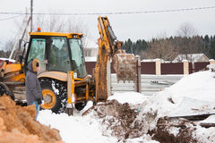 PERM, RUSSIA, DECEMBER 15.2015: excavator working on a construction site, dig a trench for fence Royalty Free Stock Image