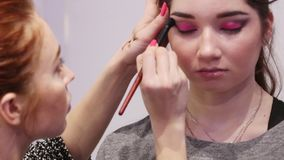 PERM, RUSSIA - FEB 12, 2017: Makeup artist with model release applies black eyeshadow for model at Wedding Fair Perm 2017 stock footage