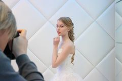 PERM, RUSSIA - FEB 12, 2017: Photographer shoots blonde bride in Royalty Free Stock Photography