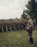 PERM, RUSSIA - JULY 30, 2016: Historical reenactment of World War II, summer, 1942. Soviet officer in front of the line of soldier Royalty Free Stock Photography