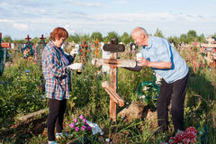 Perm, Russia - July 13.2016: Man and woman paint a wooden cross Royalty Free Stock Photo
