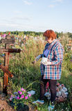 Perm, Russia - July 13.2016: Woman paints a wooden cross Royalty Free Stock Photo