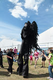 PERM, RUSSIA - JUN 15, 2013: Black angel on stilts and children. Stock Photography
