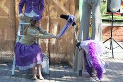 PERM, RUSSIA - JUN, 23, 2014: Woman feeds bird puppet Stock Photos