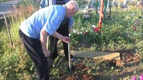 Perm, Russia - 13 luglio 2016: Due uomini stabiliscono un banco circa una tomba stock footage