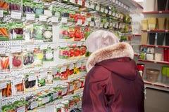 Perm, Russia - 4 marzo 2016: La donna sceglie i semi dei fiori fotografia stock