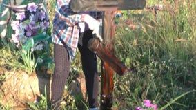Perm, Russie - 13 juillet 2016 : La femme peint une croix en bois clips vidéos