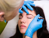 Permanent eyebrow make up - cosmetician preparing client for pro. Permanent eyebrow make up - close up of cosmetician preparing client for procedure stock photos