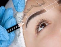 Permanent maak wenkbrauwen van mooie vrouw met dikke brows in schoonheidssalon goed royalty-vrije stock foto