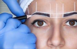 Permanent maak wenkbrauwen van mooie vrouw met dikke brows in schoonheidssalon goed stock foto