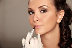 Permanent make-up. Professional permanent makeup applying on grey Royalty Free Stock Photography
