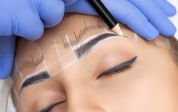 Permanent make-up for eyebrows of beautiful woman with thick brows in beauty salon. Closeup beautician doing tattooing eyebrow stock images