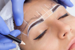 Permanent make-up for eyebrows of beautiful woman with thick brows in beauty salon. Closeup beautician doing tattooing eyebrow royalty free stock photography