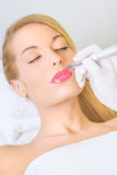 Permanent make-up on lips. Cosmetologist applying permanent make up on lips Royalty Free Stock Photo