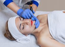 Permanent make-up for red Lips of beautiful woman in beauty salon. Closeup beautician doing tattooing Lips royalty free stock photos