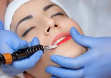 Permanent make-up for red Lips of beautiful woman in beauty salon. stock photos