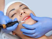 Permanent make-up for red Lips of beautiful woman in beauty salon. Closeup beautician doing tattooing Lips royalty free stock images