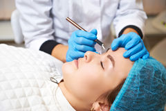 Permanent make-up wizard makes eyebrow correction procedure. Microblading Stock Photo