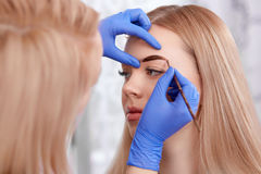 Permanent makeup of eyebrows for blonde woman. Royalty Free Stock Photos