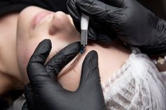 Permanent Makeup For Eyebrows. Microblading brow. Beautician Doing Eyebrow Tattooing For Female Face. Beautiful young. Microblading work flow in a beauty salon royalty free stock image