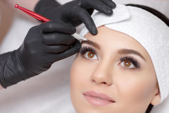 Permanent makeup eyebrows. Mikrobleyding eyebrows workflow in a beauty salon. Cosmetologist applying a special permanent makeup on a woman`s eyebrows stock photos