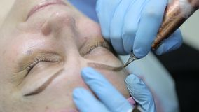 Permanent makeup. Permanent tattooing of eyebrows. Cosmetologist applying permanent make up on eyebrows- eyebrow tattoo stock video footage