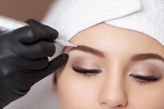 Permanent makeup. Tattooing of eyebrows. Permanent makeup. Permanent tattooing of eyebrows. Cosmetologist applying permanent make up on eyebrows- eyebrow tattoo Stock Photography