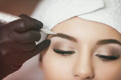 Permanent makeup. Tattooing of eyebrows. Permanent makeup. Permanent tattooing of eyebrows. Cosmetologist applying permanent make up on eyebrows- eyebrow tattoo Royalty Free Stock Images