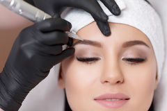 Permanent makeup. Tattooing of eyebrows. Permanent makeup. Permanent tattooing of eyebrows. Cosmetologist applying permanent make up on eyebrows- eyebrow tattoo stock photos