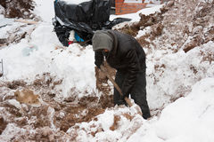 PERMANENT, RUSLAND, 15 DECEMBER 2015: de arbeider graaft een geul voor moeras Stock Afbeeldingen