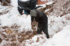 PERMANENT RYSSLAND, DECEMBER 15 2015: arbetaren gräver ett dike för kärr Arkivbilder