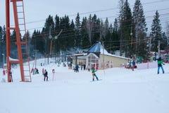 PERMANENT RYSSLAND, DECEMBER 13 2015: Folkskida och snowboarding i skidasemesterorten 'Zhebrei', Arkivbild