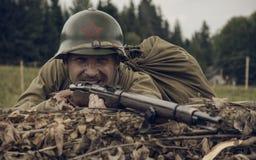 PERMANENT RYSSLAND - JULI 30, 2016: Historisk reenactment av världskrig II, sommar, 1942 Sovjetisk soldat med geväret royaltyfria bilder