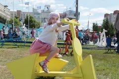 PERMANENT RYSSLAND - JUNI 13, 2013: Flicka på cykeln med triangulära hjul Arkivfoton