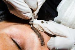 Permanent tatuera för makeup av ögonbryn Cosmetologist som applicerar permanent smink på ögonbryn arkivbild