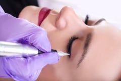 Permanente componga la procedura dell'eye-liner immagine stock