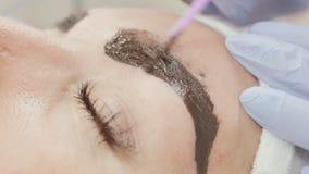 Permanente make-up Het permanente tatoeëren van wenkbrauwen Cosmetologist permanent van toepassing zijn maakt omhoog op de tatoeg stock footage