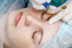 Permanente make-up, het tatoe?ren van wenkbrauwen Cosmetologist het van toepassing zijn maakt omhoog stock fotografie