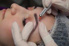 Permanente Make-up voor Wenkbrauwen Microblading brow Schoonheidsspecialist die wenkbrauw doen die voor vrouwelijk gezicht tatoeë stock foto