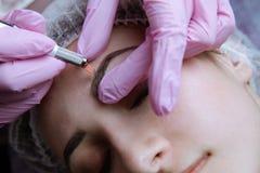 Permanente Make-up voor Wenkbrauwen Microblading brow Schoonheidsspecialist die wenkbrauw doen die voor vrouwelijk gezicht tatoeë stock fotografie